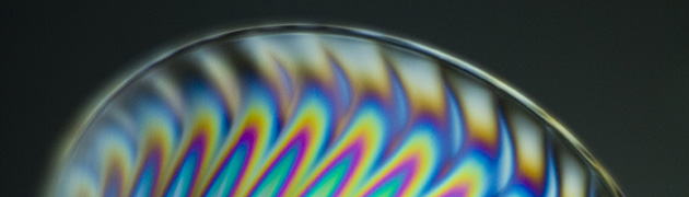 A close-up image of a clear plastic cup shining under a polarized filter