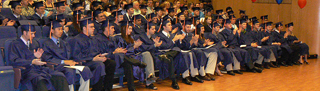 Graduates in caps and gowns seated in a lecture hall