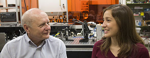 Professor Emeritus James C. Wyant sits in a holography laboratory with graduate student Maria Ruiz, the latest recipient of the Louise A. Wyant Memorial Scholarship