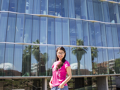 Xiaoyin Zhu stands in front of the north face of the west wing of the Meinel Building, which reflects the palm trees and planetarium across the UA Mall