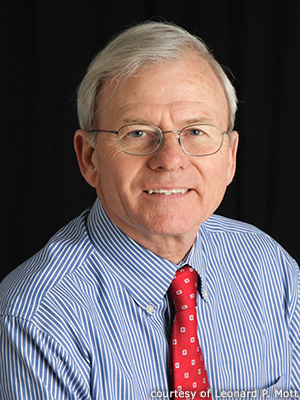 A formal portrait of Len Mott in a blue striped shirt and red tie against a black background