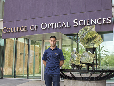 Janos Keresztes in front of the Meinel Building with the College of Optical Sciences sign in the background